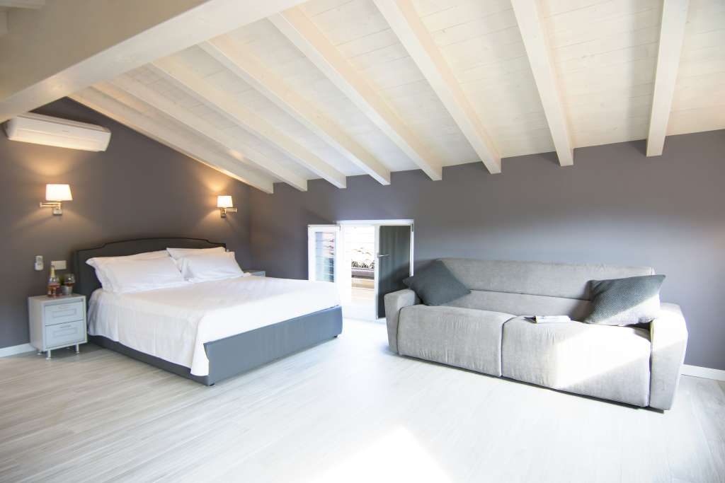 bed and sofa under the white roof