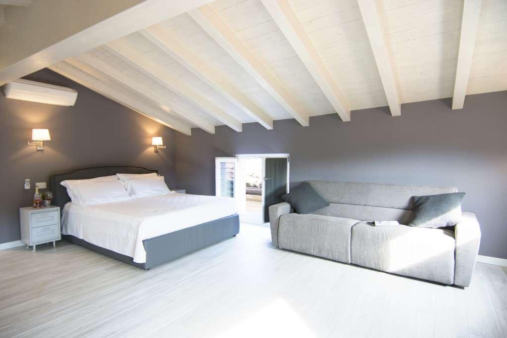 letto e divano sotto il romantico tetto bianco