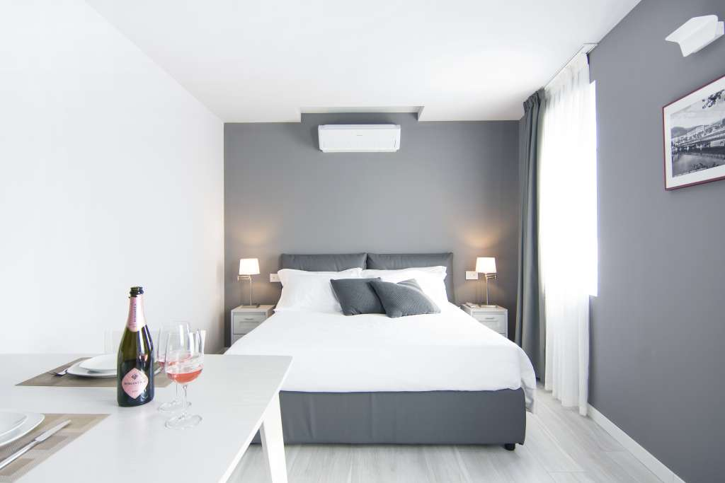 a double bed, a bottle of sparkling rose wine and a window over the city center